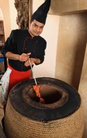 What is a Tandoor and where does Tandoori originate from?